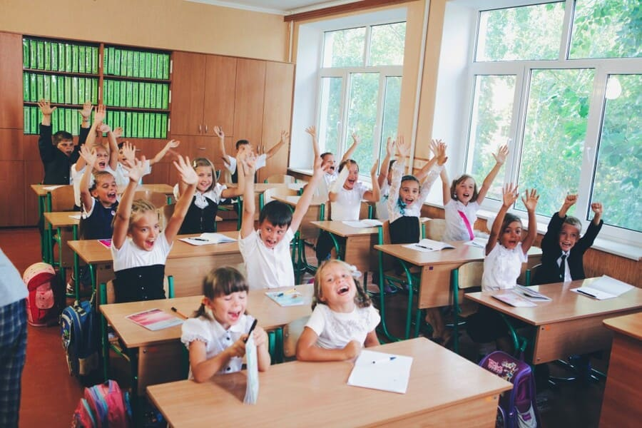 primary school with happy kids at their clean desks