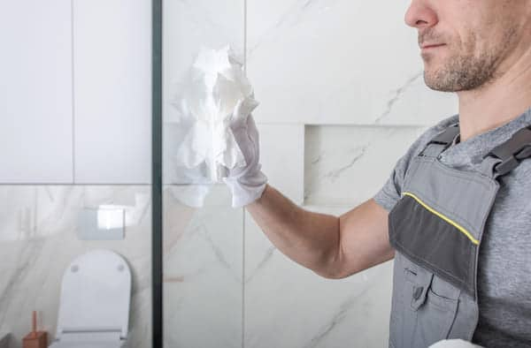 man cleaning shower with easy cleaning Nanoman Glass, water repelling