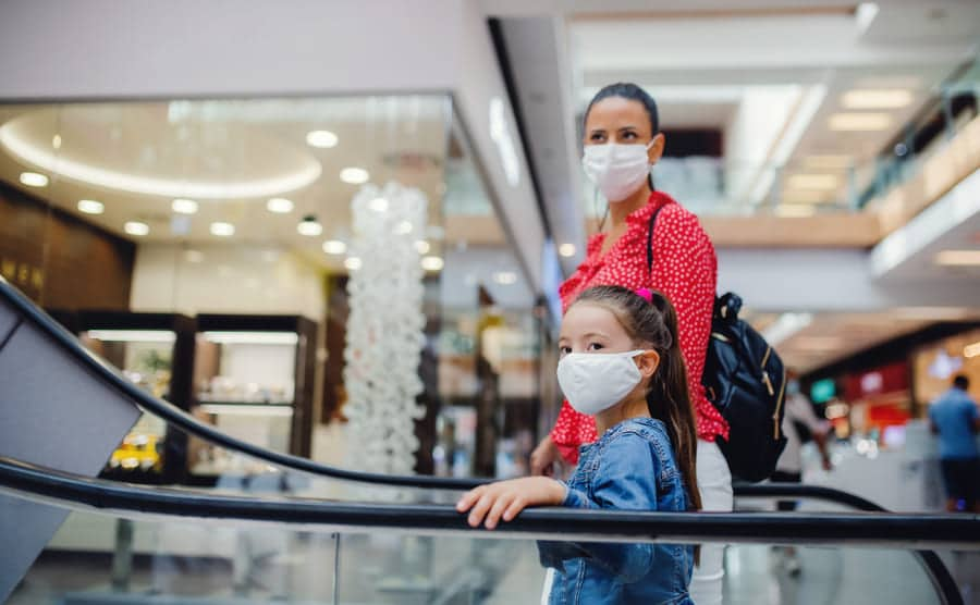 Mum and daughter wearing masks in shopping centre